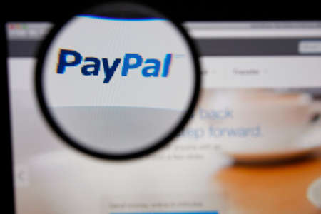 paypal: LISBON - JANUARY 14, 2014: Photo of Paypal homepage on a monitor screen through a magnifying glass.