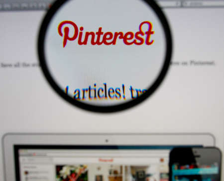 pinterest: LISBON - JANUARY 14, 2014: Photo of Pinterest homepage on a monitor screen through a magnifying glass.