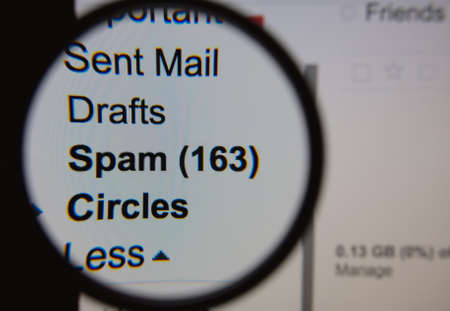 spammer: Magnifying glass showing a spam folder in the mailbox on the monitor screen.