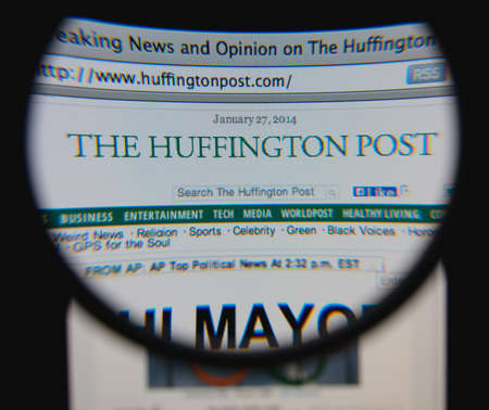 aggregator: LISBON - JANUARY 29, 2014: Photo of The Huffington Post homepage on a monitor screen through a magnifying glass.