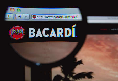 bacardi: LISBON, PORTUGAL - FEBRUARY 5, 2014: Photo of Bacardi homepage on a monitor screen through a magnifying glass.