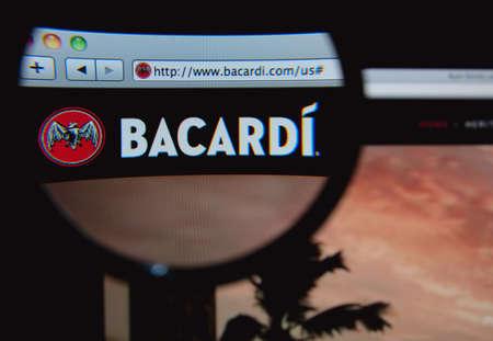 bacardi: LISBON, PORTUGAL - FEBRUARY 5, 2014: Photo of Bacardi homepage on a monitor screen through a magnifying glass.