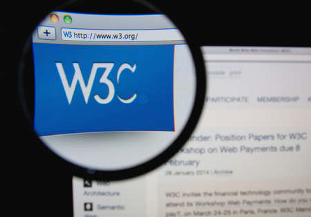 w3c: LISBON, PORTUGAL - FEBRUARY 5, 2014: Photo of the World Wide Web Consortium homepage on a monitor screen through a magnifying glass. Editorial