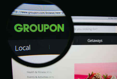 LISBON, PORTUGAL - FEBRUARY 5, 2014: Photo of Groupon homepage on a monitor screen through a magnifying glass. Groupon is a deal-of-the-day website that features discounted gift certificates.