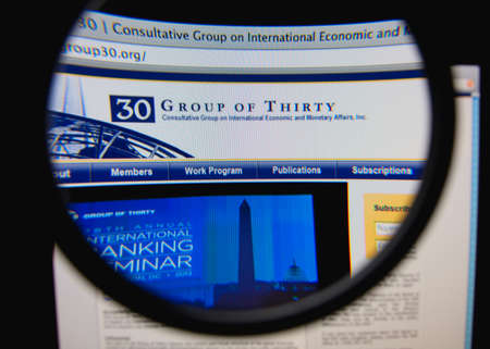 foreign bodies: LISBON, PORTUGAL - FEBRUARY 6, 2014: Photo of Group of Thirty homepage on a monitor screen through a magnifying glass. Editorial