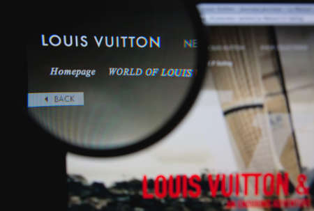 vuitton: LISBON - JANUARY 29, 2014: Photo of Louis Vuitton homepage on a monitor screen through a magnifying glass.