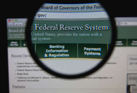 federal reserve: LISBON - JANUARY 29, 2014: Photo of Board of Governors of the Federal Reserve System homepage on a monitor screen through a magnifying glass.