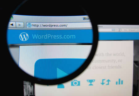 wordpress: LISBON - JANUARY 14, 2014: Photo of WordPress homepage on a monitor screen through a magnifying glass. Editorial
