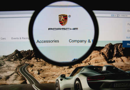 LISBON, PORTUGAL - FEBRUARY 5, 2014: Photo of Porsche homepage on a monitor screen through a magnifying glass.