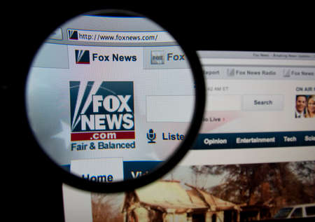 LISBON, PORTUGAL - FEBRUARY 5, 2014: Photo of Fox News homepage on a monitor screen through a magnifying glass.