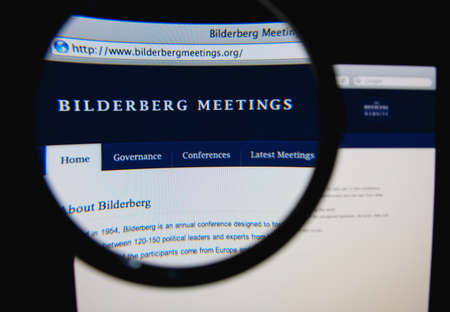 LISBON, PORTUGAL - FEBRUARY 5, 2014: Photo of Bilderberg Meetings homepage on a monitor screen through a magnifying glass.