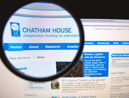 LISBON, PORTUGAL - FEBRUARY 6, 2014: Photo of the Chatham House homepage on a monitor screen through a magnifying glass. Фото со стока - 34840988