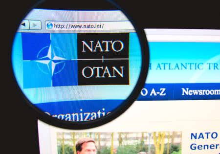 nato: LISBON, PORTUGAL - FEBRUARY 6, 2014: Photo of NATO homepage on a monitor screen through a magnifying glass.