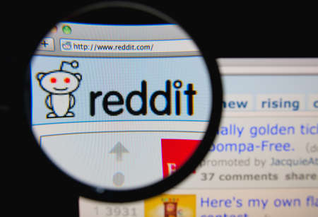 LISBON, PORTUGAL - FEBRUARY 6, 2014: Photo of Reddit homepage on a monitor screen through a magnifying glass. Éditoriale