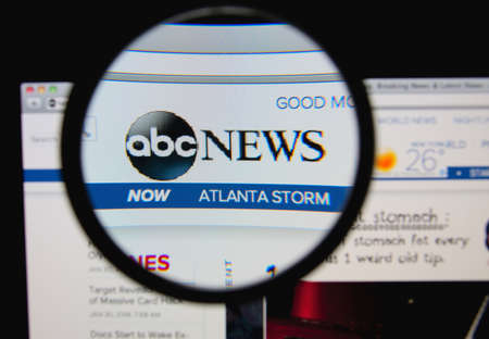 tv network: LISBON, PORTUGAL - FEBRUARY 8, 2014: Photo of ABC News homepage on a monitor screen through a magnifying glass.