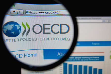 LISBON, PORTUGAL - FEBRUARY 6, 2014: Photo of Organisation for Economic Co-operation and Development homepage on a monitor screen through a magnifying glass. 에디토리얼