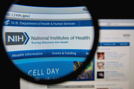 LISBON, PORTUGAL - FEBRUARY 8, 2014: Photo of the National Institutes of Health homepage on a monitor screen through a magnifying glass.