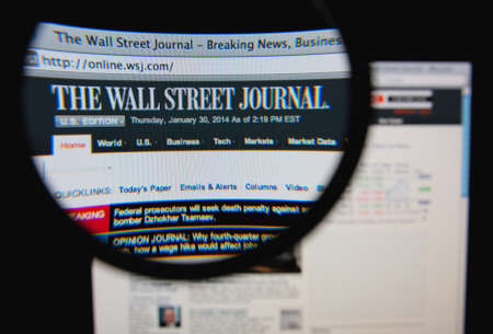 journals: LISBON, PORTUGAL - FEBRUARY 8, 2014: Photo of The Wall Street Journal homepage on a monitor screen through a magnifying glass.