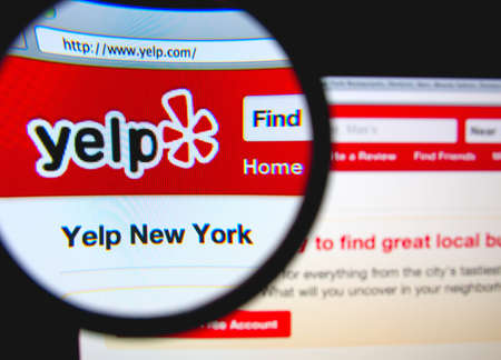 LISBON, PORTUGAL - FEBRUARY 8, 2014: Photo of Yelp homepage on a monitor screen through a magnifying glass. 報道画像