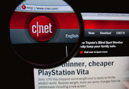 product reviews: LISBON, PORTUGAL - FEBRUARY 8, 2014: Photo of CNET homepage on a monitor screen through a magnifying glass.