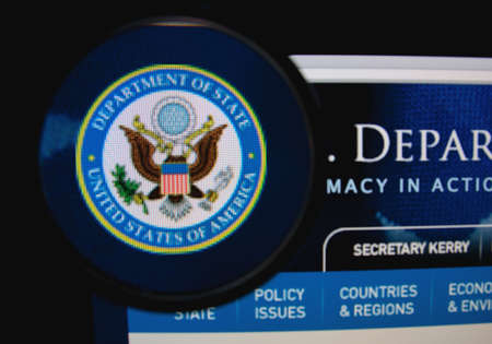 federal states: LISBON, PORTUGAL - FEBRUARY 8, 2014: Photo of the U.S. Department of State homepage on a monitor screen through a magnifying glass.