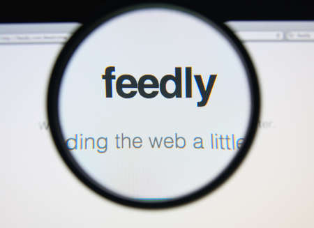 aggregator: LISBON, PORTUGAL - FEBRUARY 17, 2014: Feedly homepage through a magnifying glass.