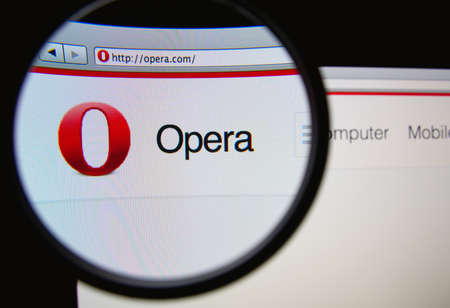 web browser: LISBON, PORTUGAL - FEBRUARY 17, 2014: Photo of Opera homepage on a monitor screen through a magnifying glass.