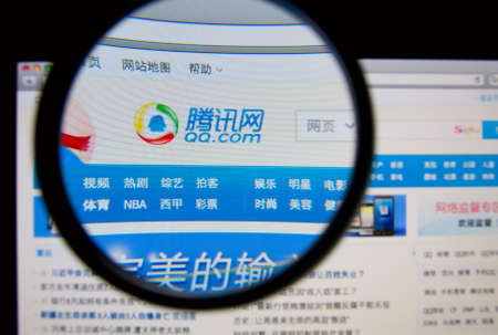web sites: LISBON, PORTUGAL - FEBRUARY 17, 2014: Photo of QQ homepage on a monitor screen through a magnifying glass. Editorial