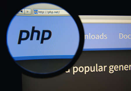 scripting: LISBON, PORTUGAL - FEBRUARY 17, 2014: Photo of PHP homepage on a monitor screen through a magnifying glass.