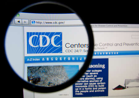 disease control: LISBON, PORTUGAL - FEBRUARY 17, 2014: The United States Centers for Disease Control and Prevention homepage through a magnifying glass.