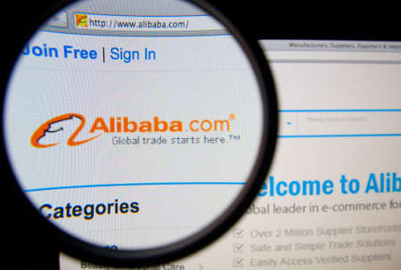 web portal: LISBON, PORTUGAL - FEBRUARY 17, 2014: Alibaba homepage on a monitor screen through a magnifying glass.