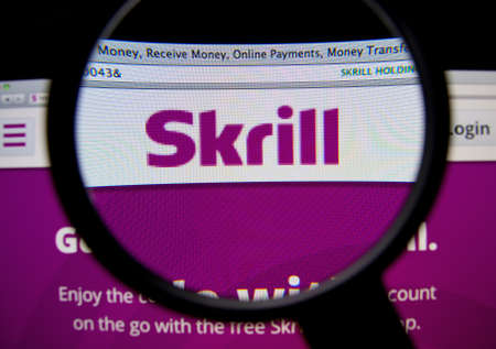 e systems: LISBON, PORTUGAL - FEBRUARY 19, 2014: Skrill homepage through a magnifying glass.