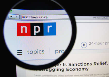 LISBON, PORTUGAL - FEBRUARY 17, 2014: Photo of the National Public Radio homepage on a monitor screen through a magnifying glass.