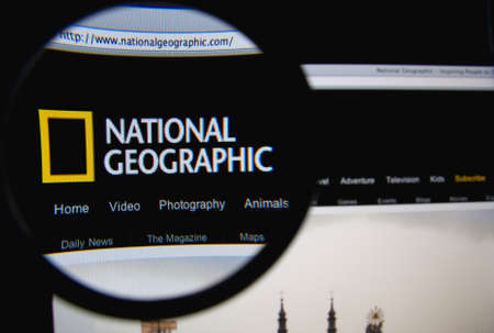 LISBON, PORTUGAL - FEBRUARY 19, 2014: The National Geographic Society homepage through a magnifying glass. Редакционное
