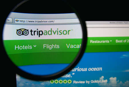 LISBON, PORTUGAL - FEBRUARY 19, 2014: TripAdvisor homepage through a magnifying glass.
