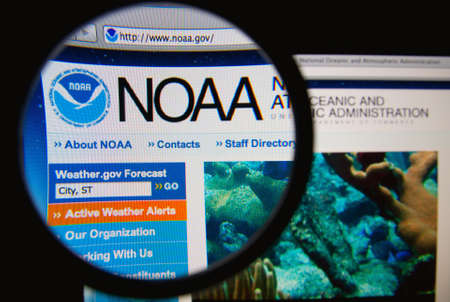 oceanic: LISBON - FEBRUARY 19, 2014: National Oceanic and Atmospheric Administration homepage through a magnifying glass. Editorial