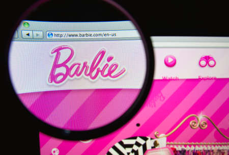 barbie: LISBON, PORTUGAL - FEBRUARY 19, 2014: Photo of Barbie homepage on a monitor screen through a magnifying glass.