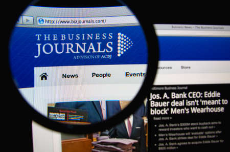 journals: LISBON, PORTUGAL - FEBRUARY 19, 2014: Photo of The Business Journals homepage on a monitor screen through a magnifying glass.