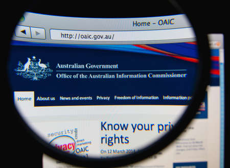 commissioner: LISBON, PORTUGAL - FEBRUARY 19, 2014: The Office of the Australian Information Commissioner (OAIC) homepage through a magnifying glass.