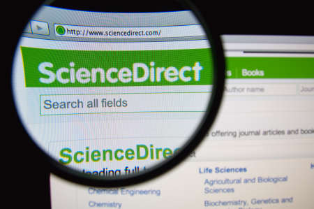 LISBON, PORTUGAL - FEBRUARY 21, 2014: Photo of ScienceDirect homepage on a monitor screen through a magnifying glass.