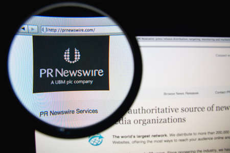pr: LISBON, PORTUGAL - FEBRUARY 19, 2014: Photo of PR Newswire homepage on a monitor screen through a magnifying glass.