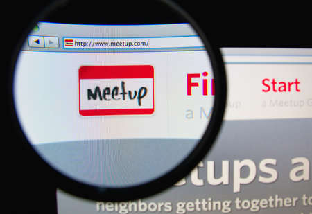 meetup: LISBON, PORTUGAL - FEBRUARY 19, 2014: Photo of Meetup homepage on a monitor screen through a magnifying glass.