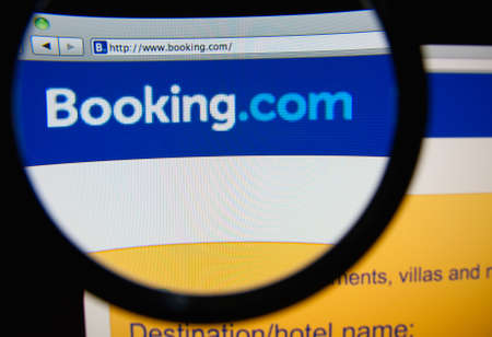 LISBON, PORTUGAL - FEBRUARY 21, 2014: Photo of Booking.com homepage on a monitor screen through a magnifying glass. 에디토리얼