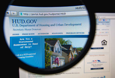 LISBON, PORTUGAL - FEBRUARY 21, 2014: Photo of the United States Department of Housing and Urban Development homepage on a monitor screen through a magnifying glass.