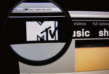 mtv: LISBON, PORTUGAL - FEBRUARY 21, 2014: Photo of MTV homepage on a monitor screen through a magnifying glass.