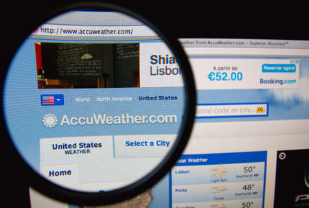 american media: LISBON, PORTUGAL - FEBRUARY 21, 2014: AccuWeather homepage through a magnifying glass. Editorial