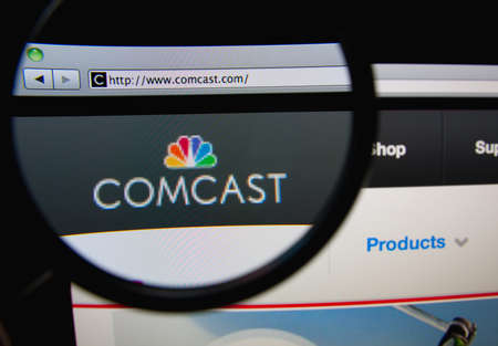 LISBON, PORTUGAL - FEBRUARY 21, 2014: Photo of Comcast Corporation homepage on a monitor screen through a magnifying glass. Фото со стока - 34844768