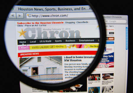 chronicle: LISBON, PORTUGAL - FEBRUARY 21, 2014: Photo of Houston Chronicle homepage on a monitor screen through a magnifying glass.