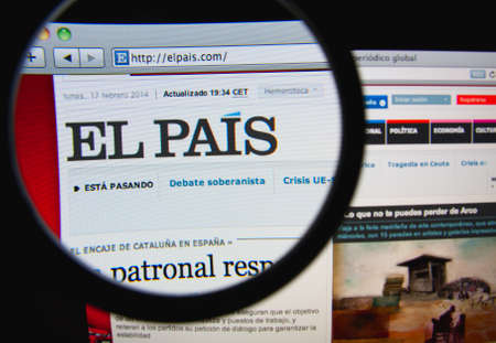LISBON, PORTUGAL - FEBRUARY 21, 2014: Photo of El Pais on a monitor screen through a magnifying glass. Редакционное