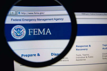 LISBON, PORTUGAL - FEBRUARY 21, 2014: Photo of Federal Emergency Management Agency homepage on a monitor screen through a magnifying glass.